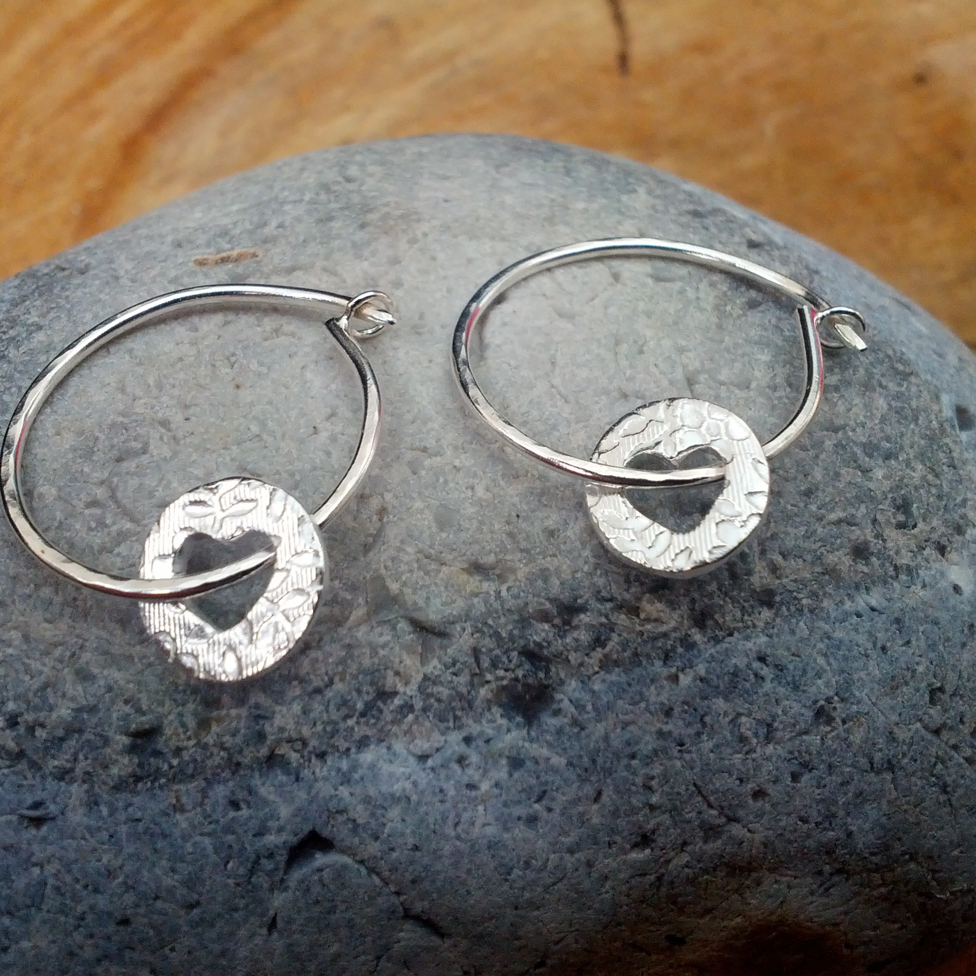 Silver hoop earrings with cut out heart dangles