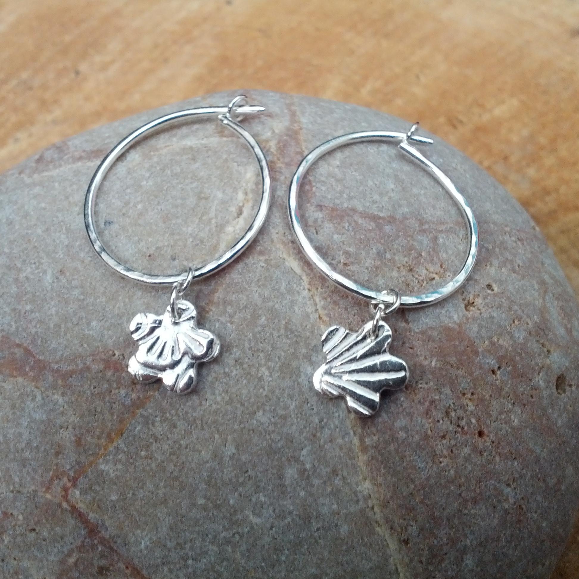 Silver hoop earrings with textured flower dangles