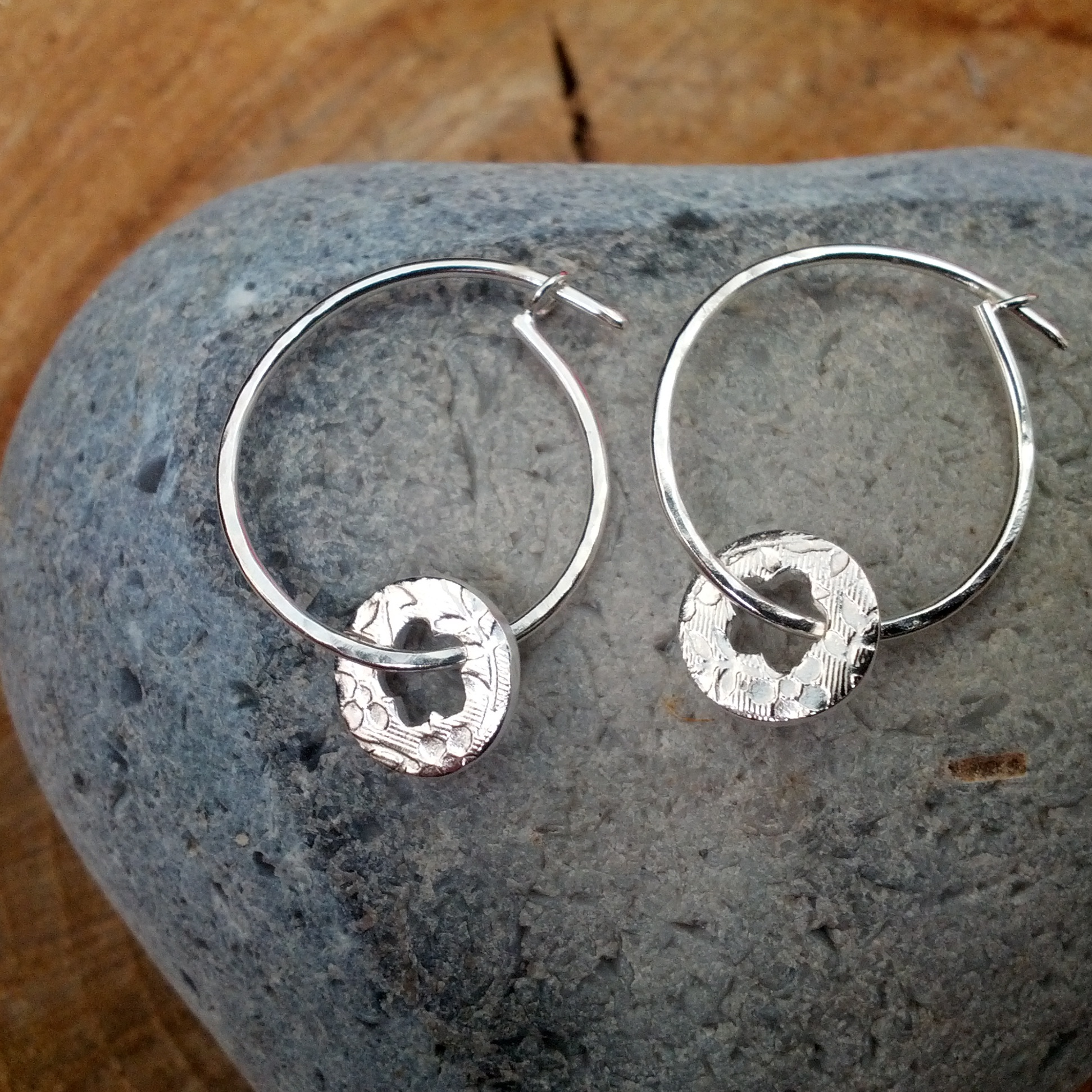 Silver hoop earrings with cut out flower dangles