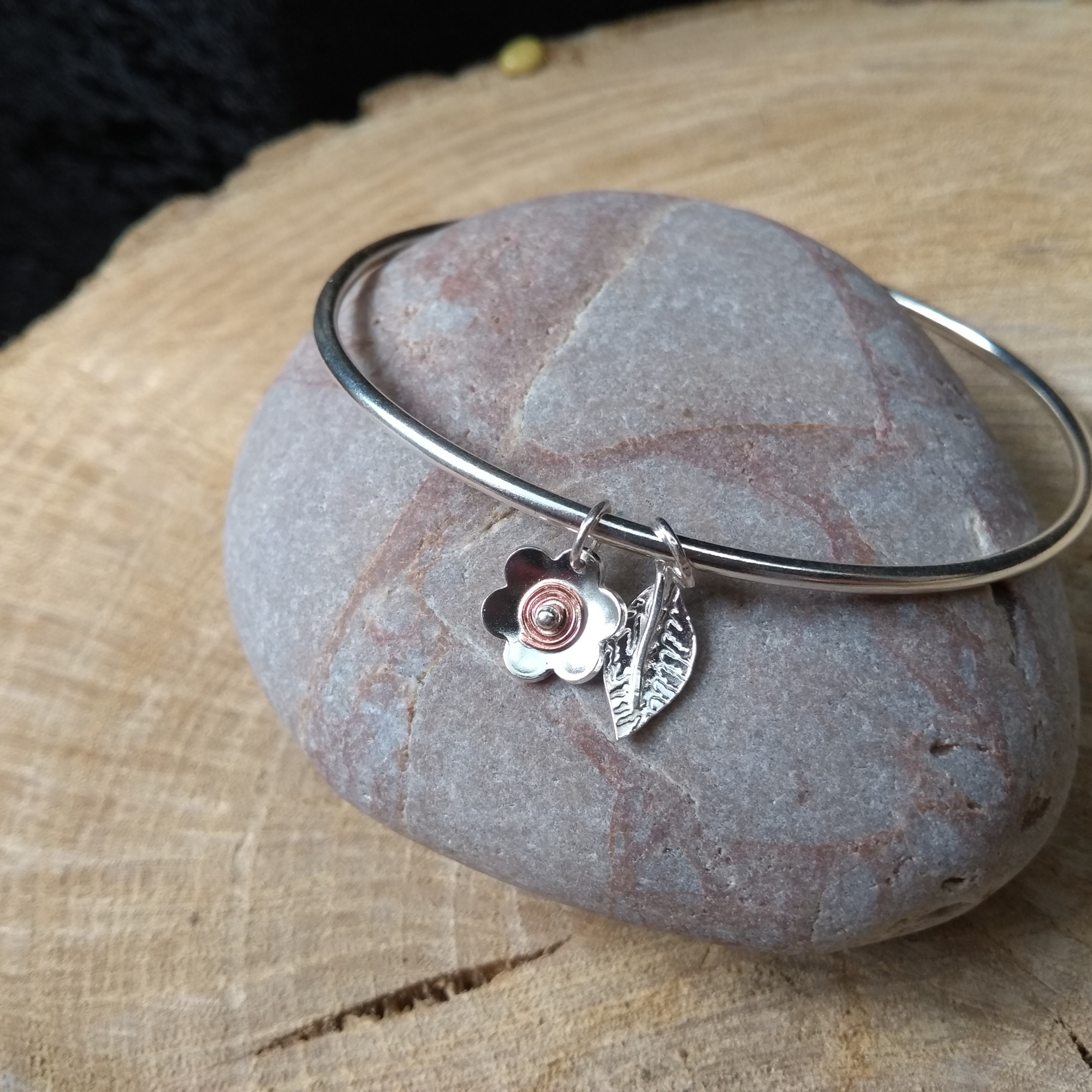 Silver bangle with silver and copper flower and leaf dangles